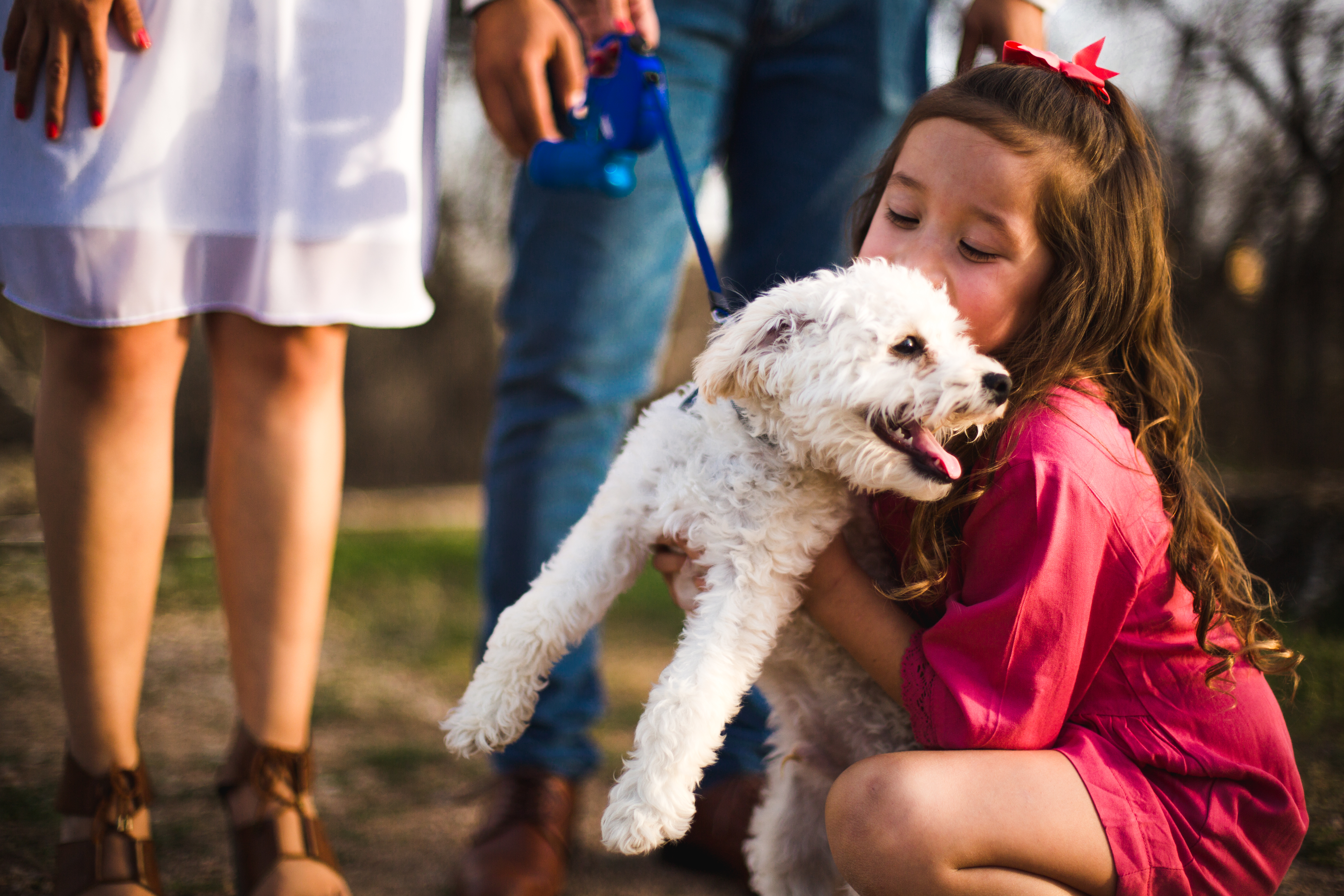 Girl hugging small white dog